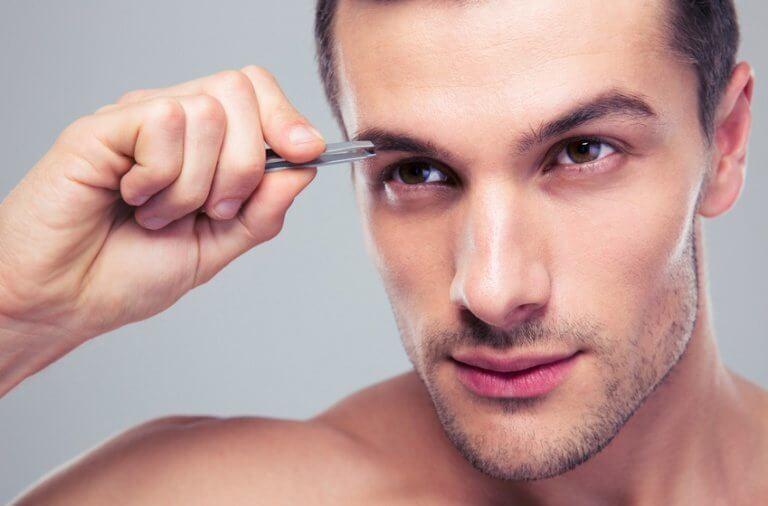 Mand plukker øjenbryn med pincet