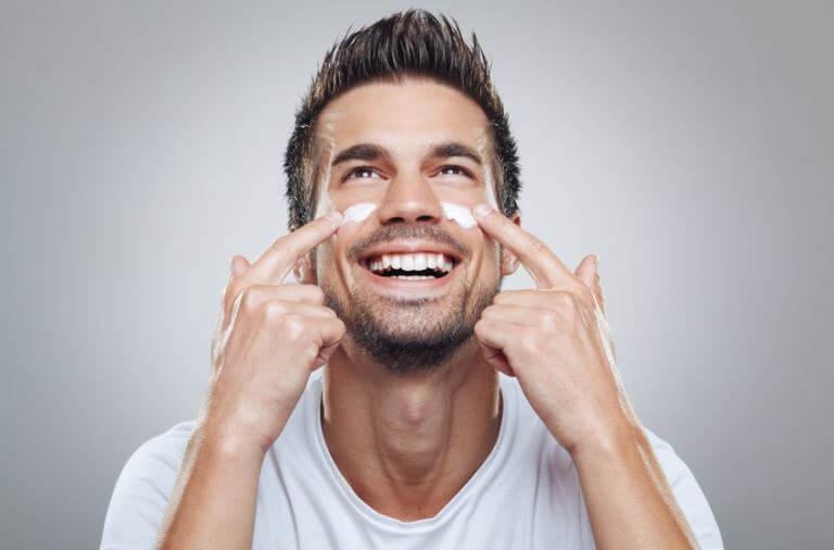 Ung mand smøre creme i ansigtet