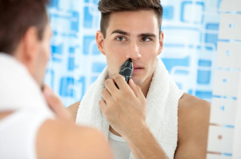 Mand fjerner hår i næsen